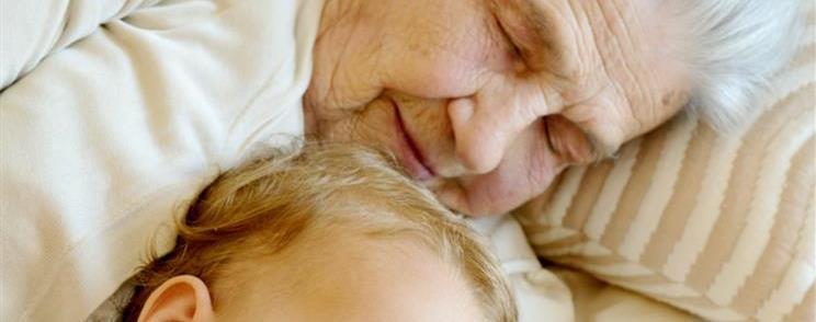 אישה מבוגרת ישנה ליד תינוק